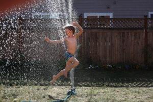 little boy jumping through sprinkler